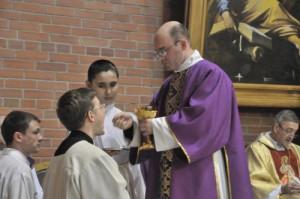 Диакон Александр Деппершмидт преподает Святое Причастие во время Святой Мессы