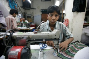 young boy working in delhi textile factory, india