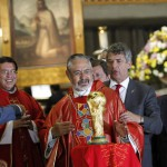 Father Diego Monroy looks at the World Cup trophy next to Spanish Football Federation President Angel Maria Villar in Mexico City