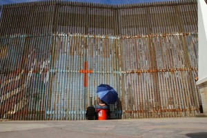 A woman talks to her relatives across a fence separating Mexico and the United States, in Tijuana